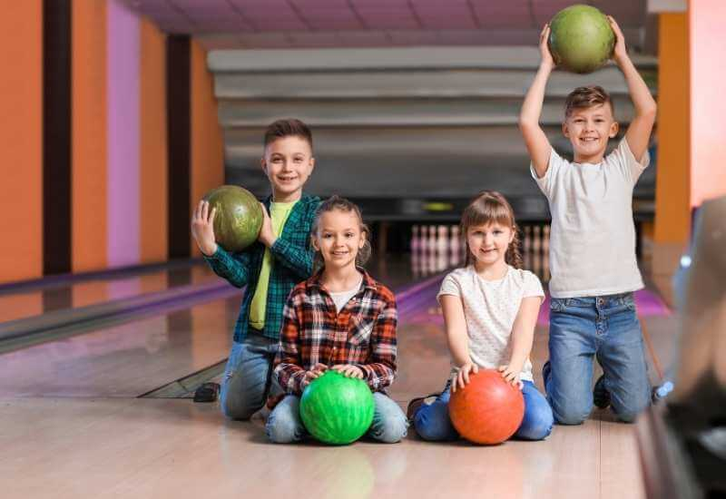 Kids are holding bowling balls